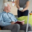 Carer giving disabled man coffee — Stock Photo #59059825