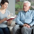 Senior care assistant reading book — Stock Photo #59060401