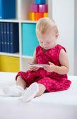 Little cute girl using phone — Stock Photo