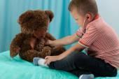 Boy examining teddy bear by stethoscope — Stock Photo