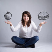 Girl with a dilemma about food — Stock Photo
