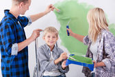 Loving family painting wall together — Stock Photo