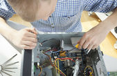 Young man repairing computer — Stock Photo