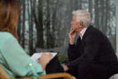 Sad man talking with psychologist — Stock Photo
