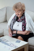 Elder woman playing solitaire — Stock Photo