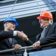 Engineers in helmets shaking hands — Stock Photo #63741267