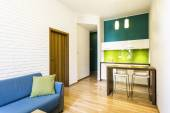 Small living room with green kitchenette — Stock Photo