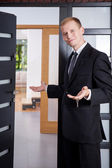 Estate agent stands at the entrance to apartment — Stock Photo