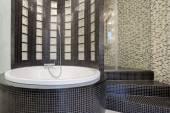 Round bathtub inside black bathroom — Stock Photo