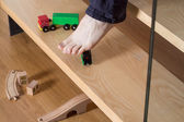 Man stepping on toys on stairs — Stock Photo