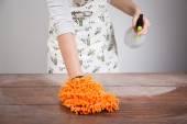 Woman cleaning dusty wooden desk — ストック写真