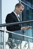 Businessman using phone outside the building — Fotografia Stock