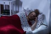 Young woman lying in bed — Stock Photo