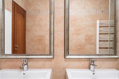 在米色的厕所里的两个洗手盆 — 图库照片