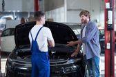 Hombre en la tienda de reparación de automóviles — Foto de Stock