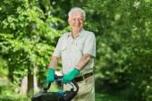 Elderly man mows a lawn — Stock Photo