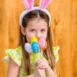 Portrait of smiling little girl with long blond hair wearing pink and white rabbit or bunny ears and holding bunch of painted colorful eggs. Easter celebrations. Wooden background. Studio portrait — Stock Photo #68422067