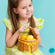 Thoughtful little girl with long blond hair wearing pink bow and holding wicker basket with yellow eggs and ribbon sitting on pink chair. Easter celebrations. Turquoise background. Studio portrait — Stock Photo #68422077