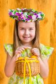 Portrait of adorable smiling little girl with long blond hair wearing floral head wreath and holding wicker basket with yellow eggs and ribbon. Easter celebrations. Wooden background. Studio portrait — Stock Photo
