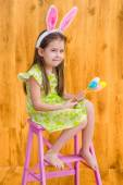 Barefooted little girl with long blond hair wearing pink white rabbit or bunny ears and holding bunch of colorful eggs sitting on pink chair. Easter celebrations. Wooden background. Studio portrait — Stock Photo