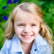 Close-up portrait of a smiling blond little girl wearing a blue jacket in sunny summer day — Stock Photo #69575495