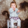 Adorable little girl with blond hair sitting on chair, laughing and clapping her hands. Studio portrait on brown grunge background — Stock Photo #70206255
