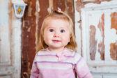 Sürpriz komik sarışın küçük kız gri gözleri iri ve dolgun yanakları ile arama yapar. Stüdyo portre grunge ahşap arka plan üzerinde — Stok fotoğraf