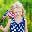Pretty pensive little girl with long curly blond hair holding an american flag and smiling on sunny day in summer park. Independence Day, Flag Day concept — Stock Photo #72173907