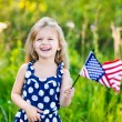 Pretty little girl with long curly blond hair holding an american flag, waving it and laughing on sunny day in summer park. Independence Day, Flag Day concept — Stock Photo #72173913
