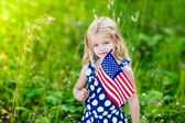 Cute smiling little girl with long curly blond hair holding an american flag on sunny day in summer park. Independence Day, Flag Day concept — Stock Photo