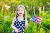 Pretty little girl with long curly blond hair holding an american flag, waving it and laughing on sunny day in summer park. Independence Day, Flag Day concept — Stock Photo