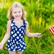 Smiling little girl with long curly blond hair holding american flag and waving it, outdoor portrait on sunny day in summer park. Independence Day, Flag Day concept — Stock Photo #73073451