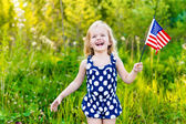 Laughing blond little girl with long curly hair holding american flag and waving it, outdoor portrait on sunny day in summer park. Independence Day, Flag Day concept — Stock Photo