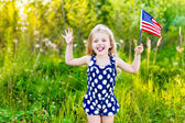 Funny little girl with long curly blond hair putting out her tongue and waving american flag, outdoor portrait on sunny day in summer park. Independence Day, Flag Day concept — Stock Photo
