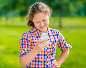 Sweet smiling teenage girl in casual clothes with smartphone in her hand, looking at screen, reading a message, using Facebook in sunny day in summer park — Stock fotografie