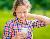 Beautiful smiling teenage girl in casual clothes with smartphone in her hand, looking at screen, reading a message, using Facebook in sunny day in summer park — Stock Photo