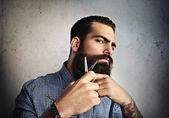 Man grooming his beard with scissors — Zdjęcie stockowe