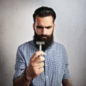 Bearded man looking at  razor — Stock Photo