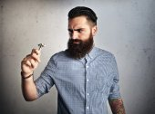 Bearded man looking at vintage shaver — Stock Photo