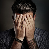 Portrait of a man hiding his face — Stock Photo