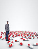 Man standing among pills — Stock Photo