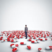 Man standing among medical pills — Stock Photo