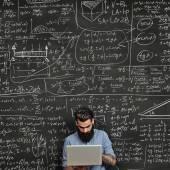Tattoed man working with laptop near chalkboard — Stock Photo
