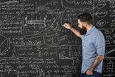 Bearded hipster writes formulas on a chalkboard — Stock Photo