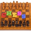 Chess board with figures with plastic letter — Stock Photo #56308849