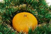 Yellow tangerine on green garland — Stock Photo