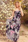 Beauty smiling woman near white magnolia — Stock Photo