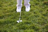Golf ball, shoes and driver in the grass — Stock Photo