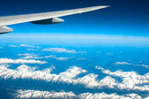 Snow-capped mountains under plane wing — Stock Photo