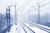 Empty electric railroad in winter forest — Stock Photo